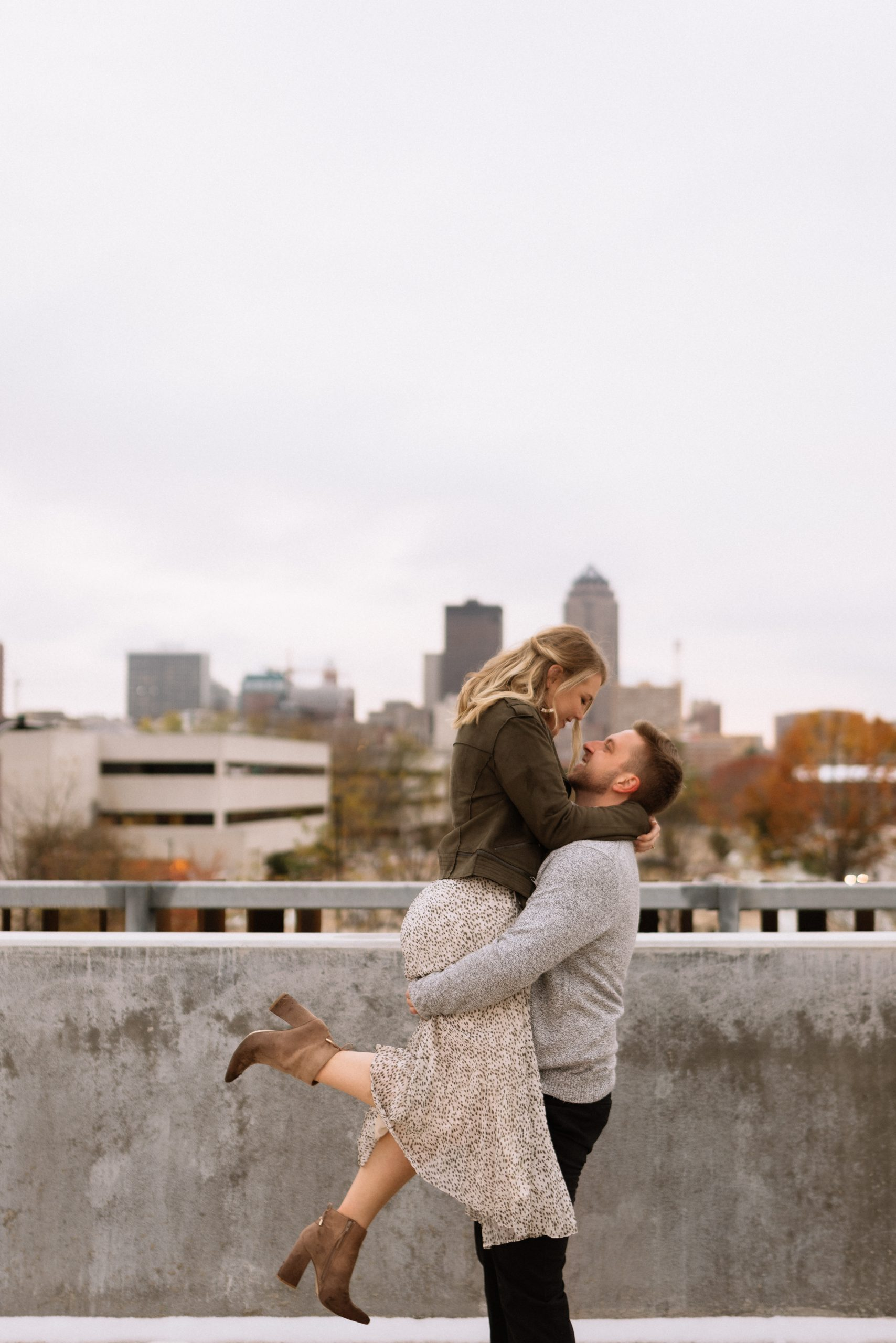 young couple engagement photoshoot in a parking lot with the city skyline in the background